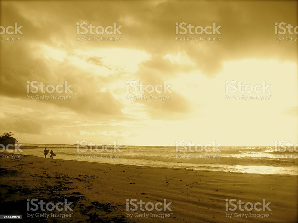 Two surfers walk beach early morning, sepia royalty-free stock photo
