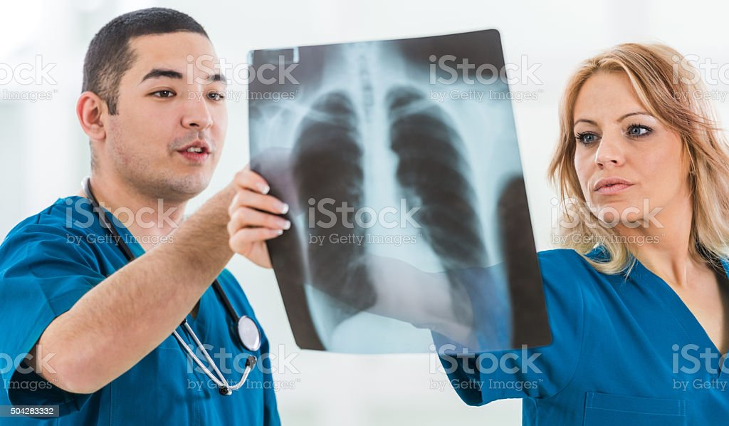 Two surgeons looking at X-ray image together. stock photo