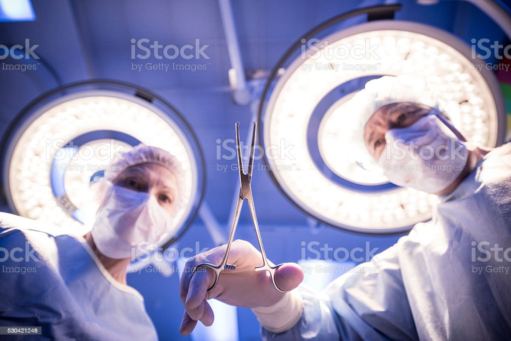 Two surgeons performing operation, point of view stock photo