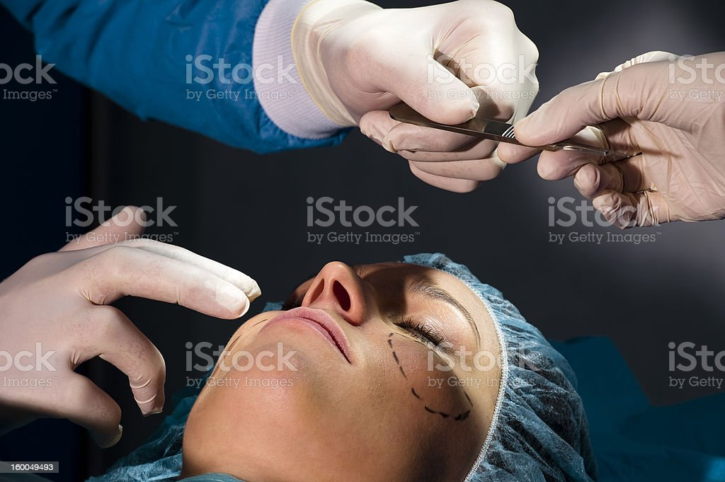 Two surgeons performing plastic surgery on woman stock photo