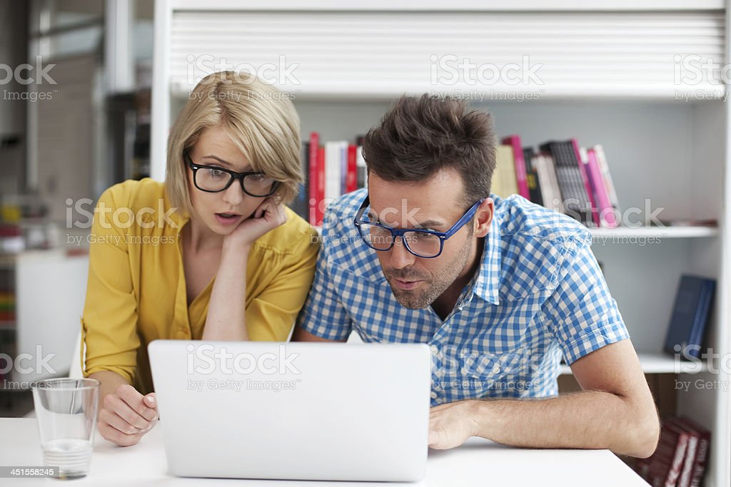 Two surprised students learning in library stock photo