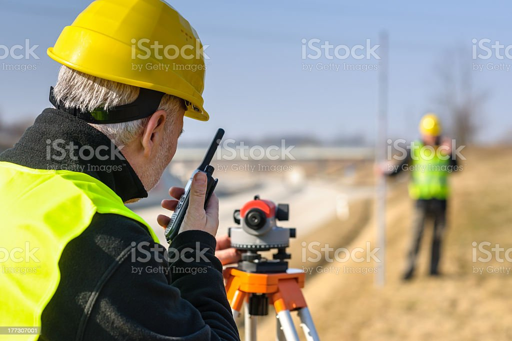 Two surveyors in reflective gear and tools outdoors royalty-free stock photo