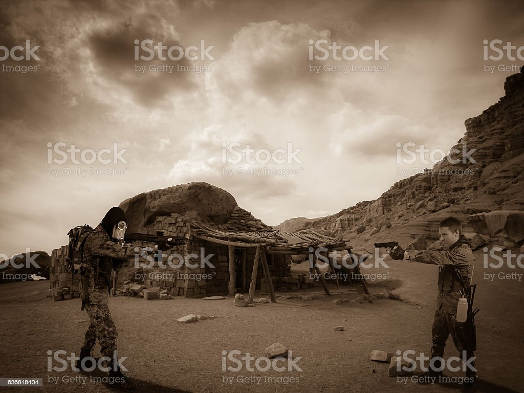 Two survivalist soldiers pointing gun at each other in desert stock photo