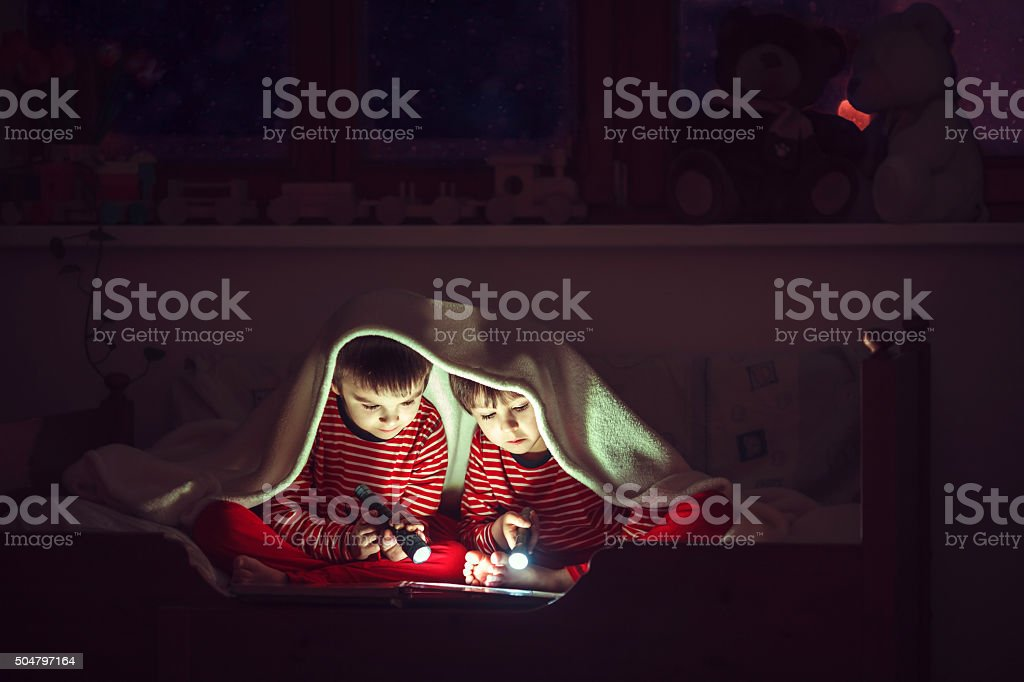 Two sweet boys, reading a book in bed after bedtime stock photo