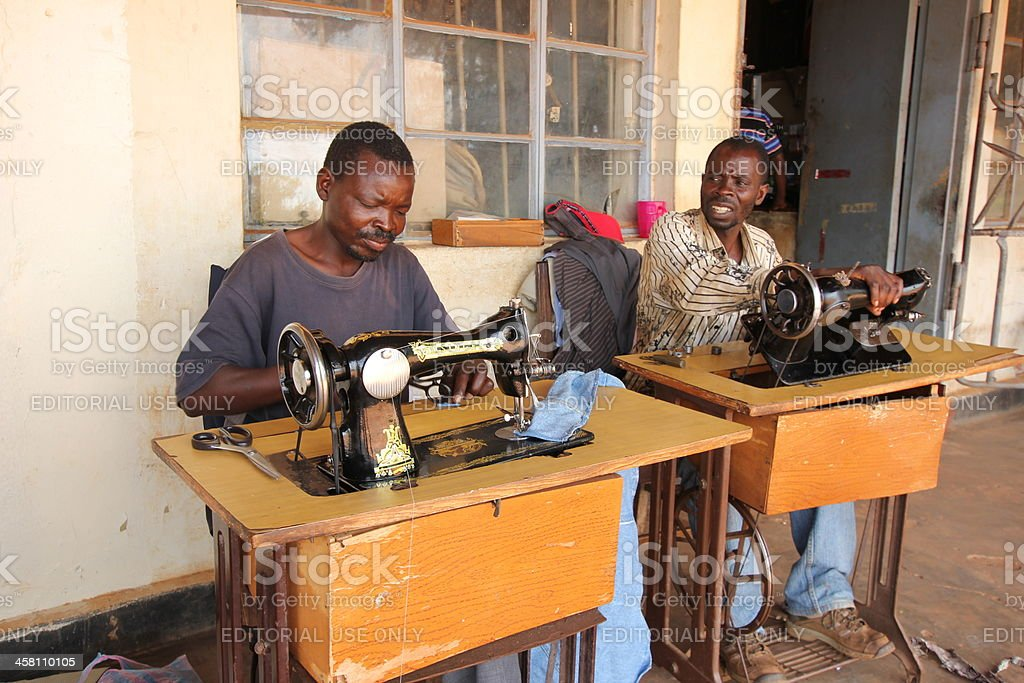 Two tailors work on their antique sewing machine royalty-free stock photo