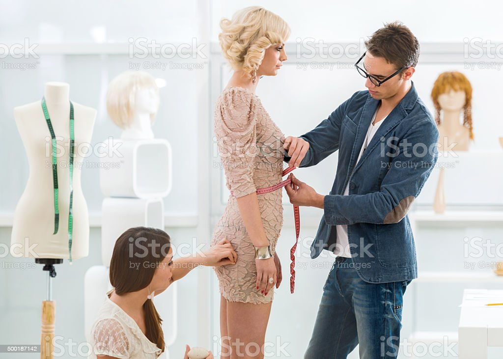 Two tailors working on customers dress in clothing design studio. stock photo