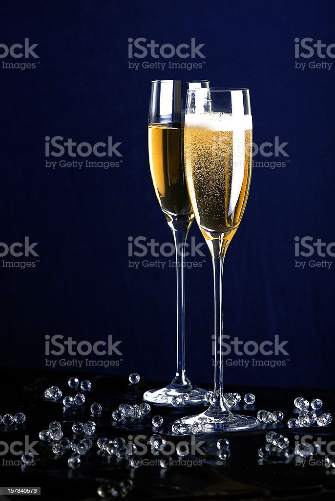 Two tall filled champagne flutes with bubbles around them stock photo