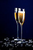Two tall filled champagne flutes with bubbles around them