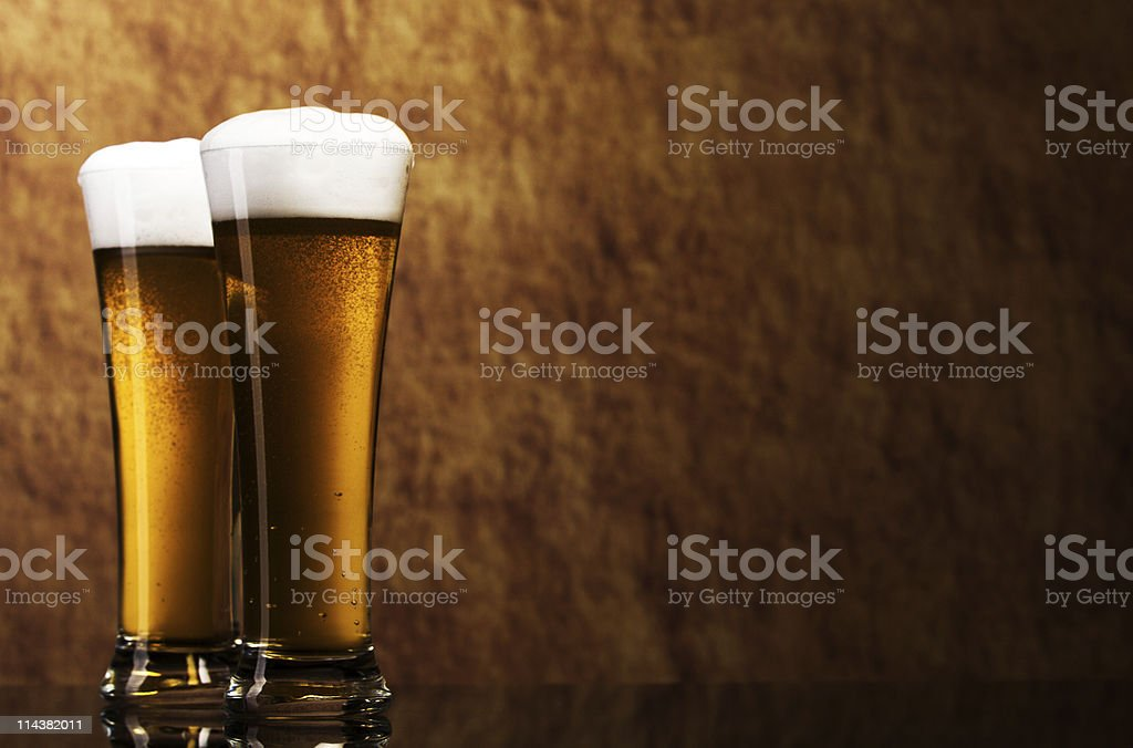 Two tall glasses of frothy beer with rough stone backdrop stock photo