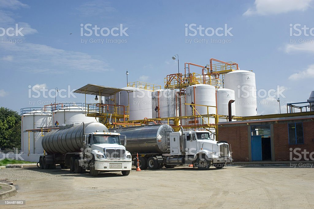 Two tanker trucks outside of a chemical storage tank stock photo