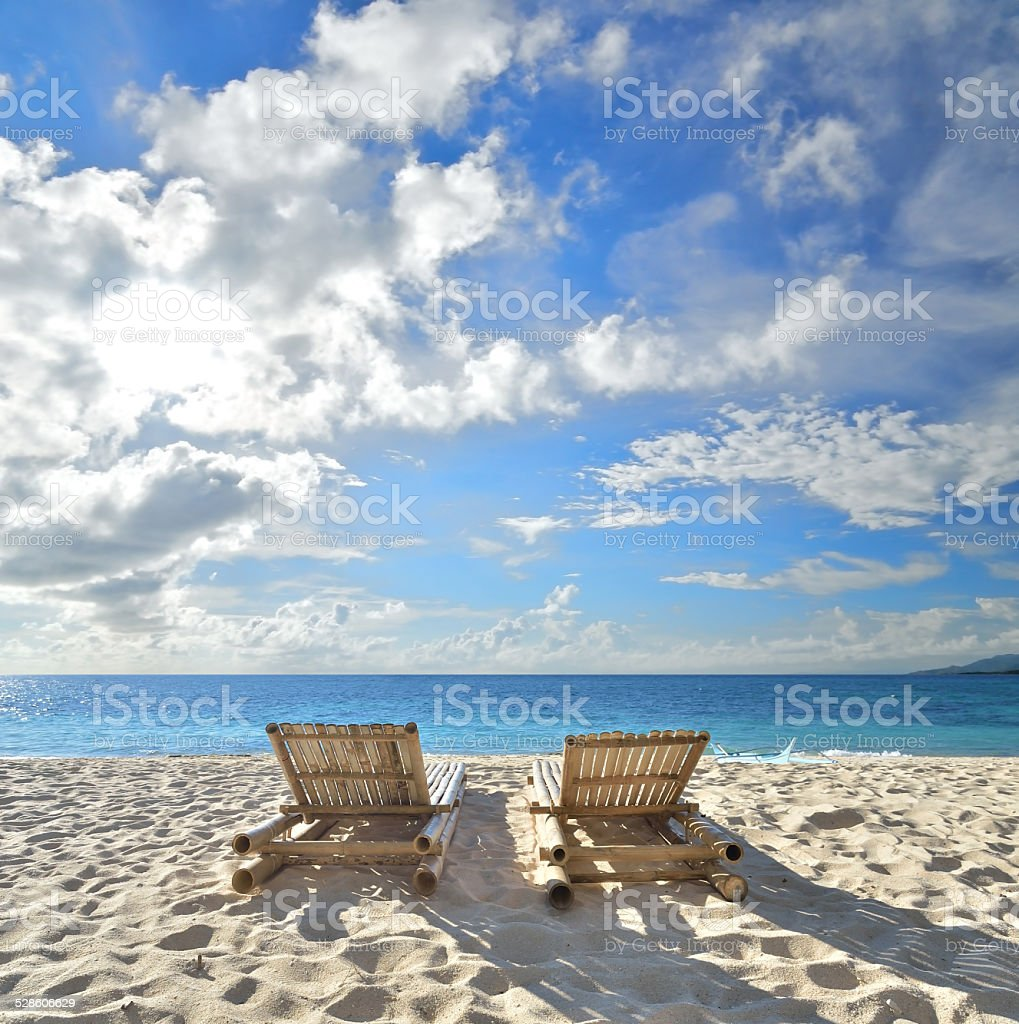 Two tanning beds at tropical sandy beach stock photo
