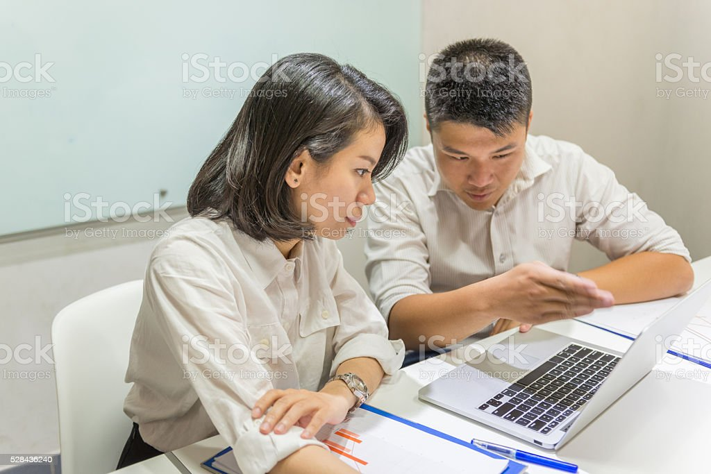 Two teammate analysing and discussing data on laptop stock photo