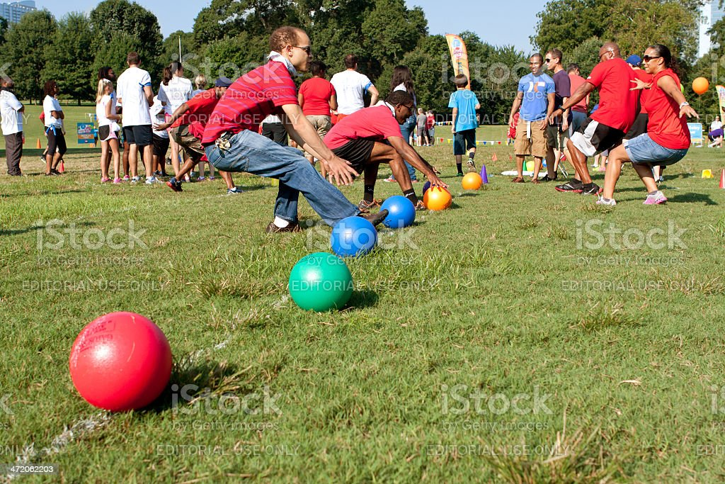 Two Teams Sprint For Balls To Begin Dodge Ball Game stock photo