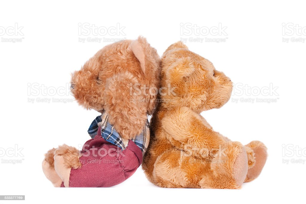 Two teddy bears, sitting back to back. stock photo