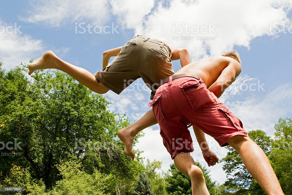 Two teenage boys bouncing high in the air stock photo