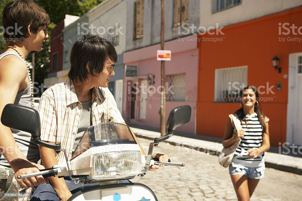Two teenage boys (14-17) by moped looking at teenage girl (16-18) royalty-free stock photo