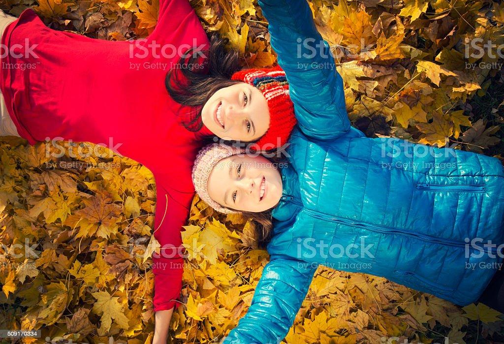 Two teenage girls among yellow leaves royalty-free stock photo