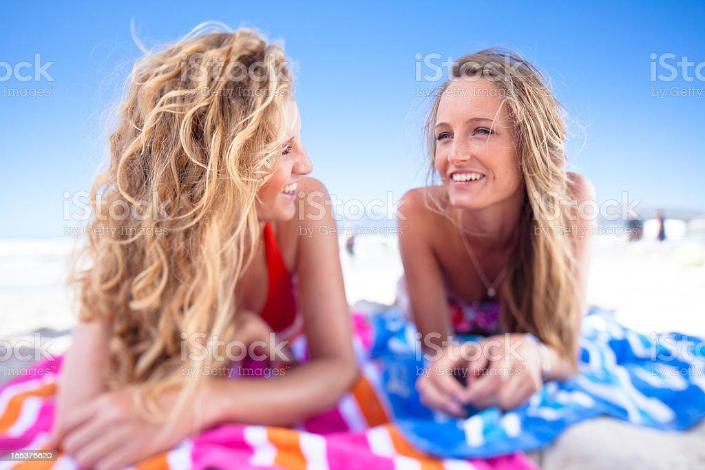 Two teenage girls gossip and sunbathe on Muizenberg beach royalty-free stock photo