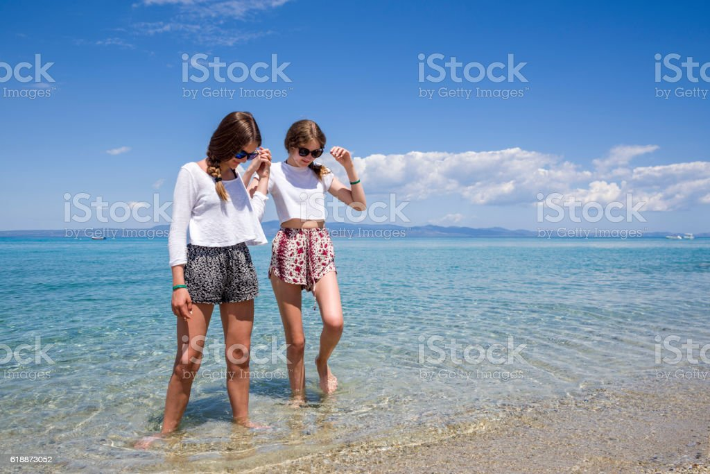 Two teenage girls holding hands at the sea stock photo