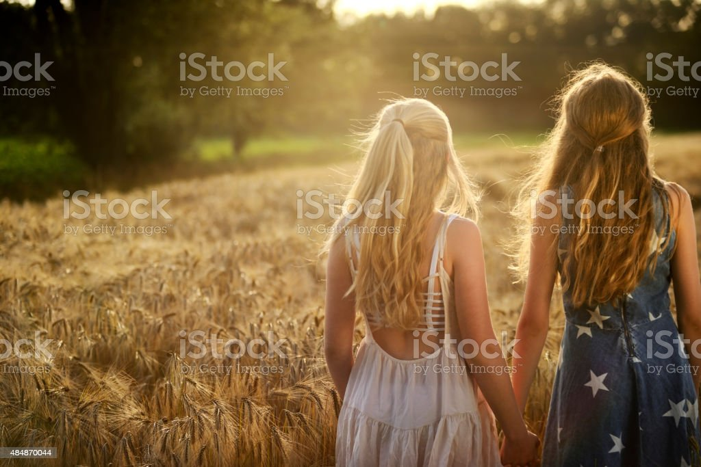 Two teenage girls holding hands in a barley field stock photo