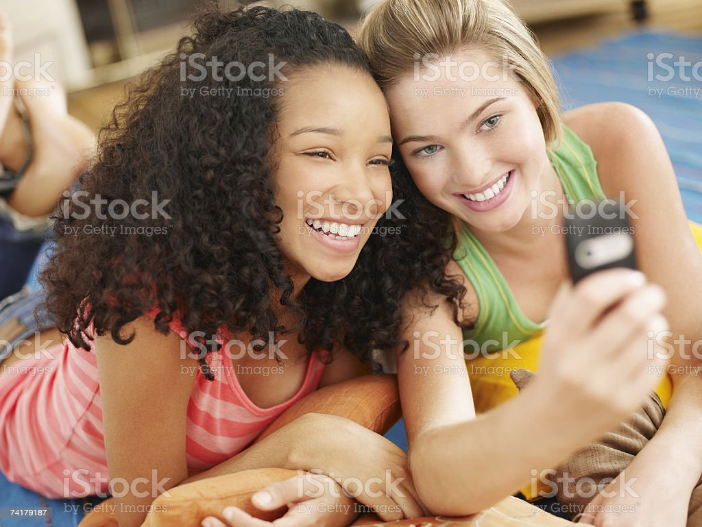 Two teenage girls lying down looking at cell phone smiling royalty-free stock photo