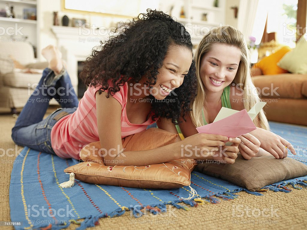 Two teenage girls lying down on floor looking at note card with envelope smiling royalty-free stock photo