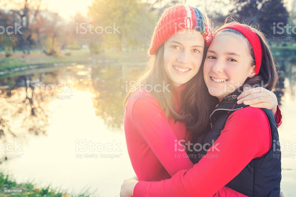 Two teenage girls posing against sunset royalty-free stock photo