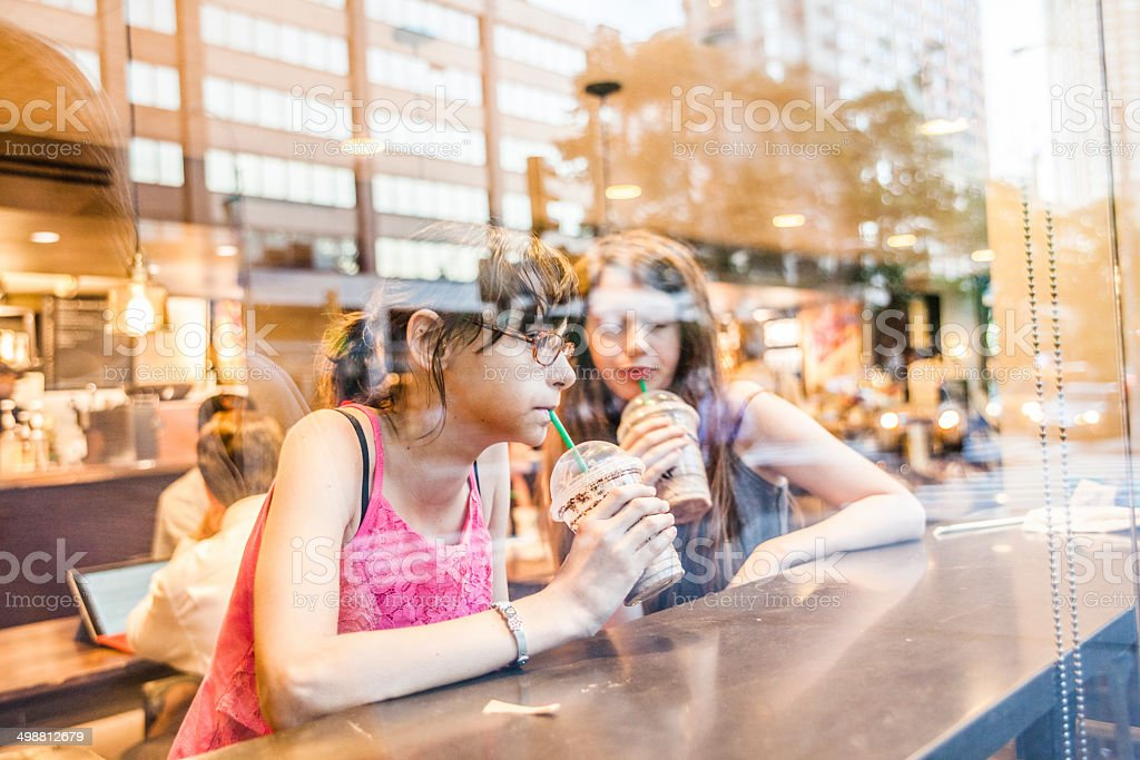 Two teenage girls, sisters, drinks iced coffee in a cafe stock photo