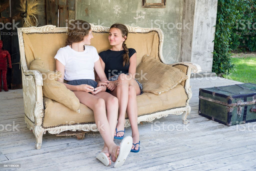 Two teenage girls sitting on vintage sofa stock photo