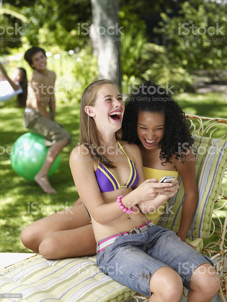 Two teenage girls sitting outdoors in summer with cell phone laughing royalty-free stock photo