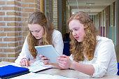 Two teenage girls studying in corridor of school