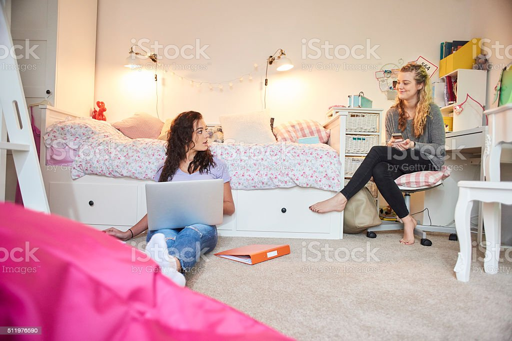 two teenage girls studying in their bedroom stock photo