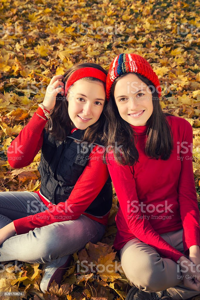 Two teenage laughing among yellow leaves royalty-free stock photo