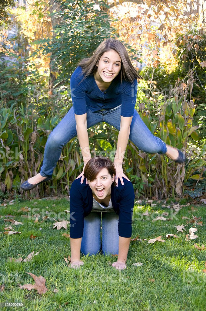 Two Teenage Sisters Playing Leap Frog in The Park stock photo