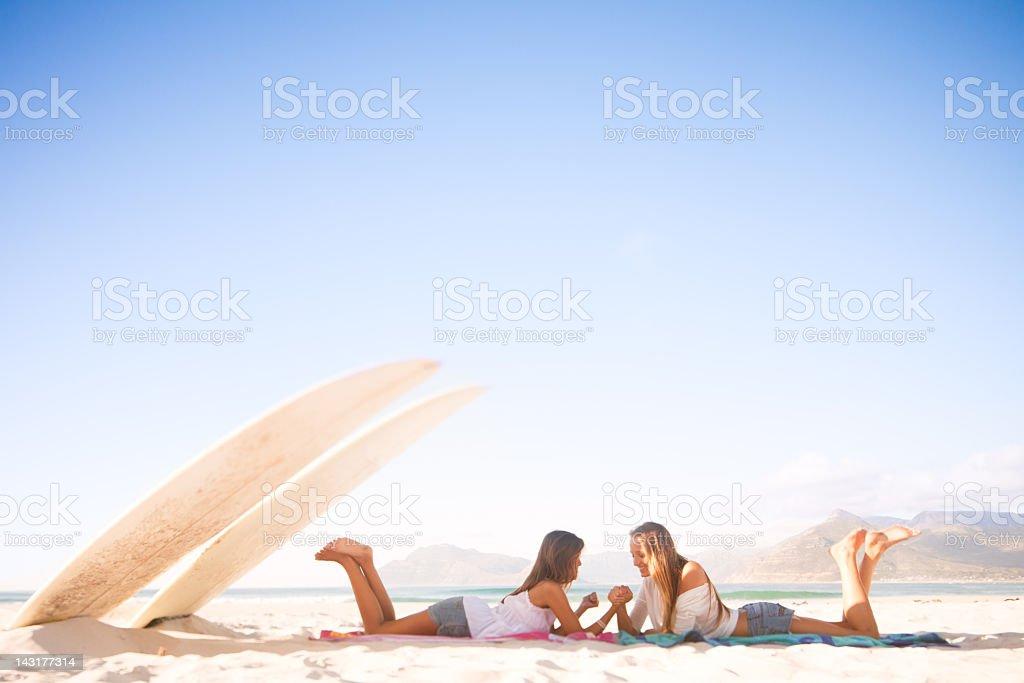 Two teenage surfer girls arm wrestling stock photo