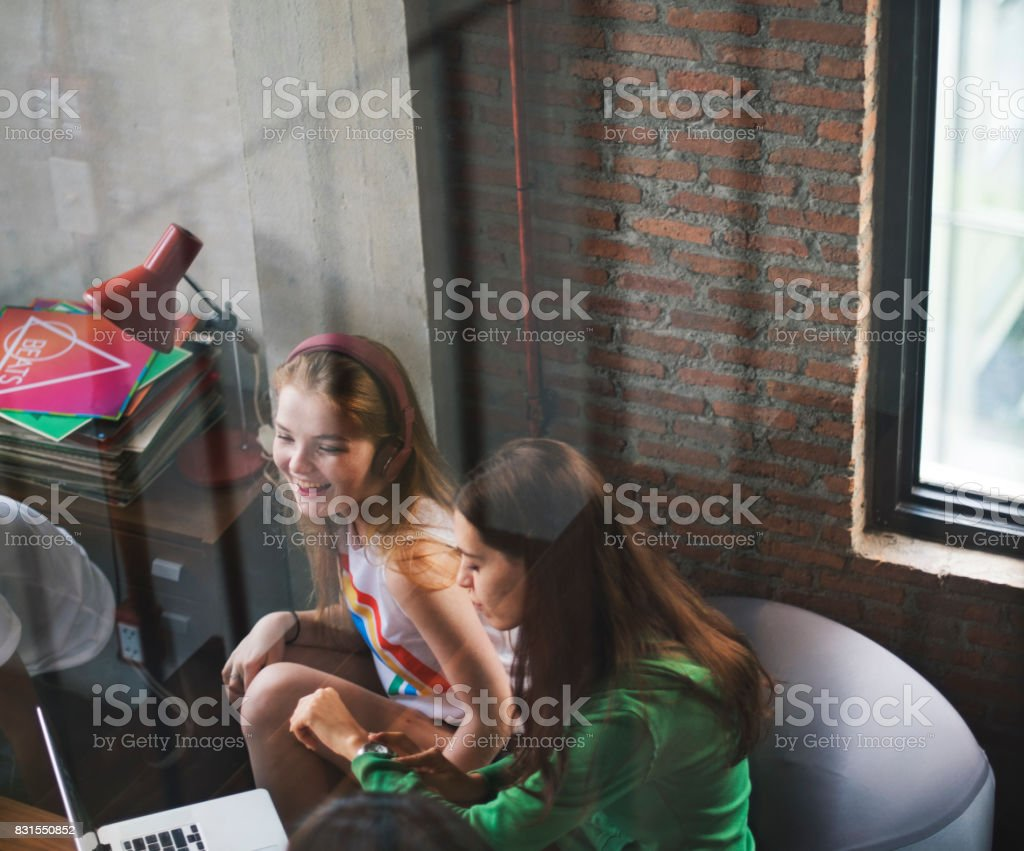 Two teenager girl sitting talking stock photo