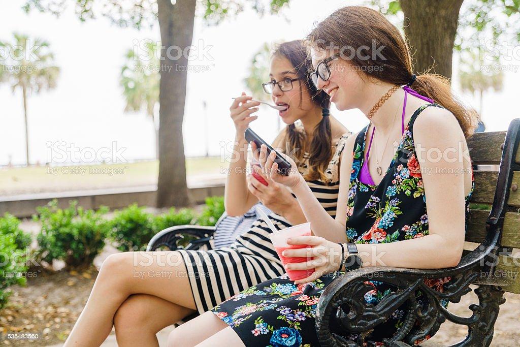 Two teenager girls eats icecream in park in Charleston stock photo