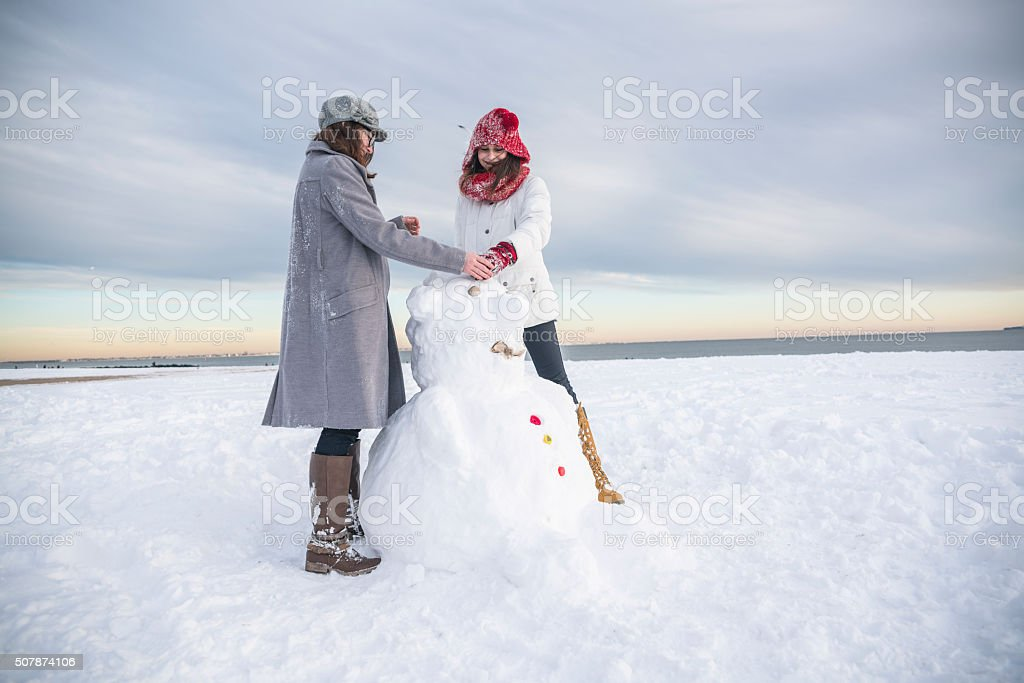 Two teenager girls, friends, make the snowman at the beach stock photo