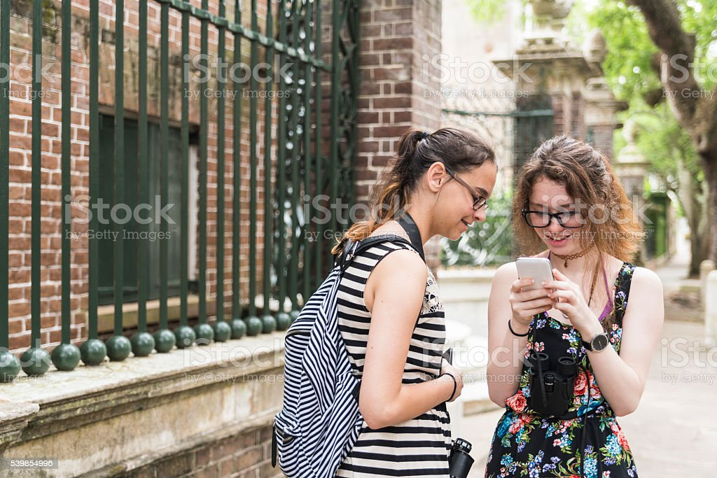 Two teenager girls looks smartphone at street in historic Charleston stock photo