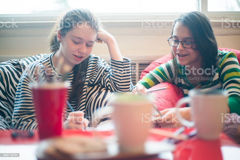 Two teenager girls play noughts and crosses stock photo