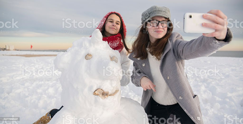 Two teenager girls, sisters, make selfie with the snowman stock photo