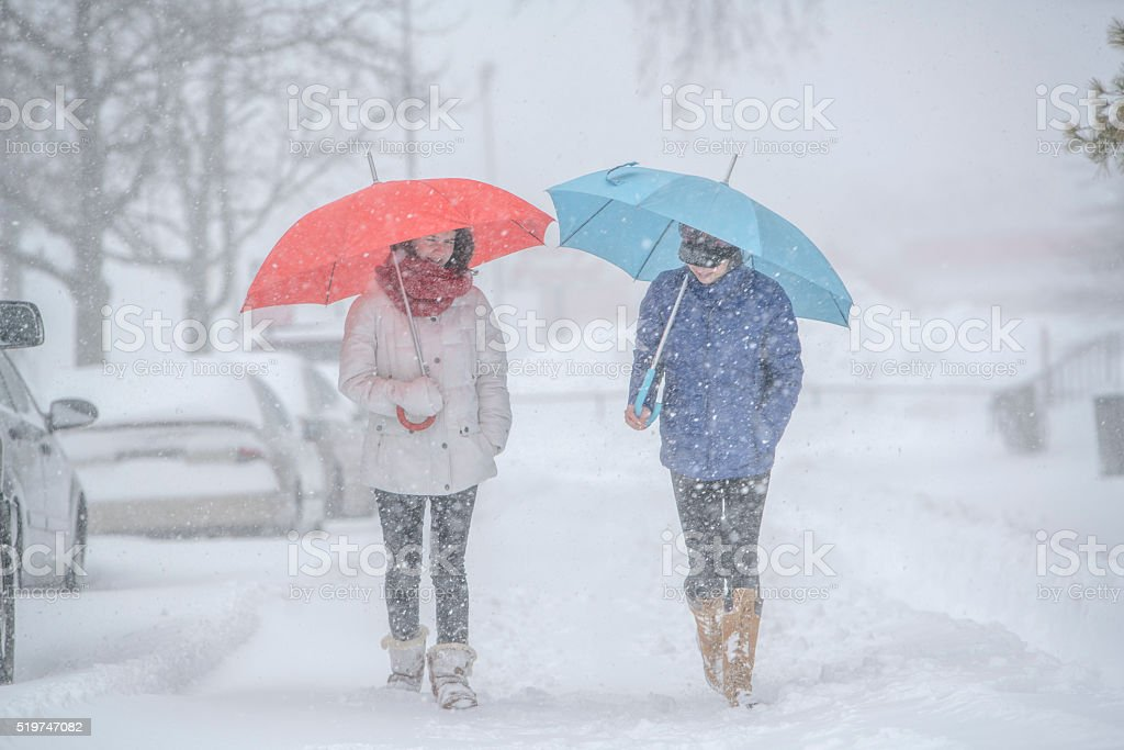 Two teenager girls with umbrellas under snowfall at the street stock photo