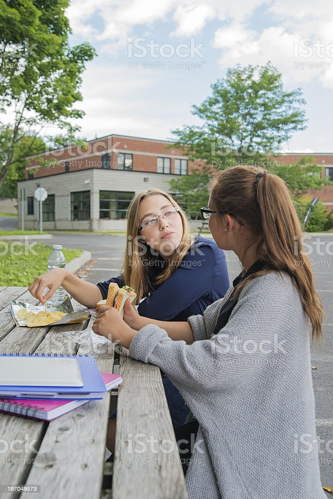 Two teenagers having lunch in high school backyard. royalty-free stock photo