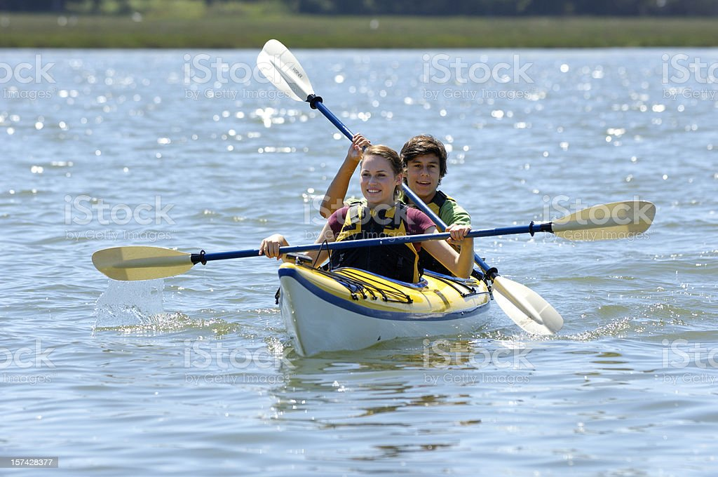 Two teenagers in kayak on water stock photo