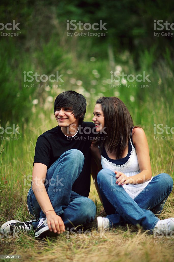Two Teenagers Sitting in Field royalty-free stock photo