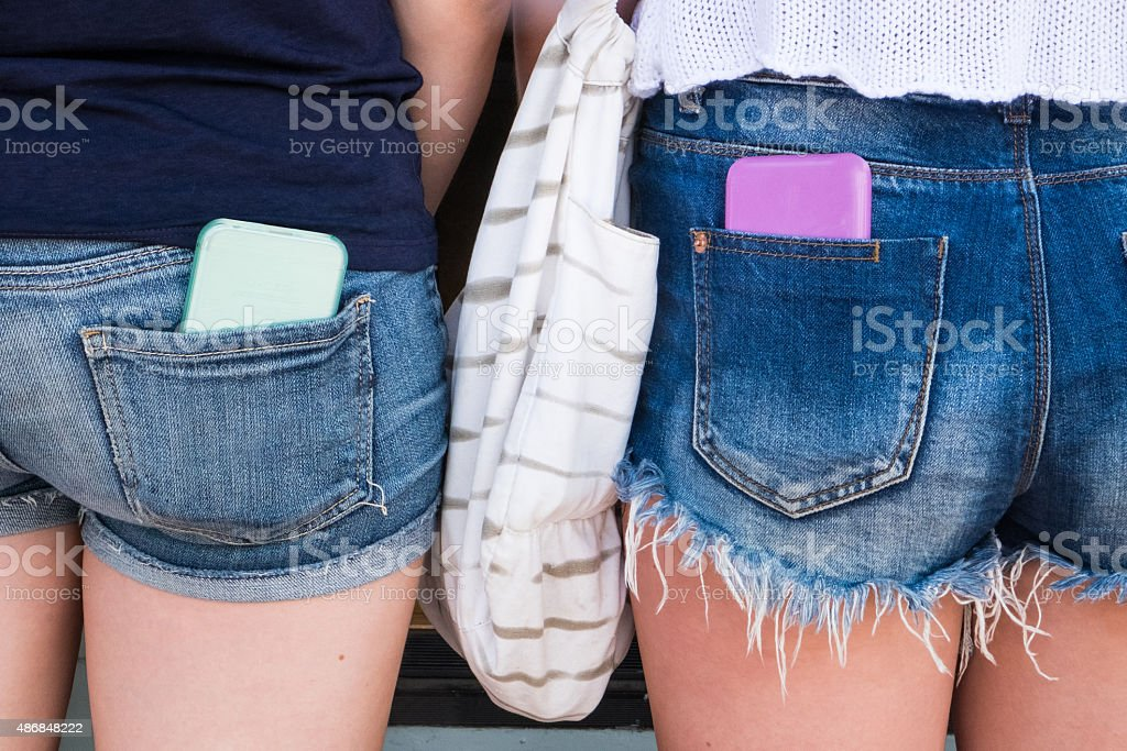 Two Teenagrs In Shorts With Cell Phones stock photo