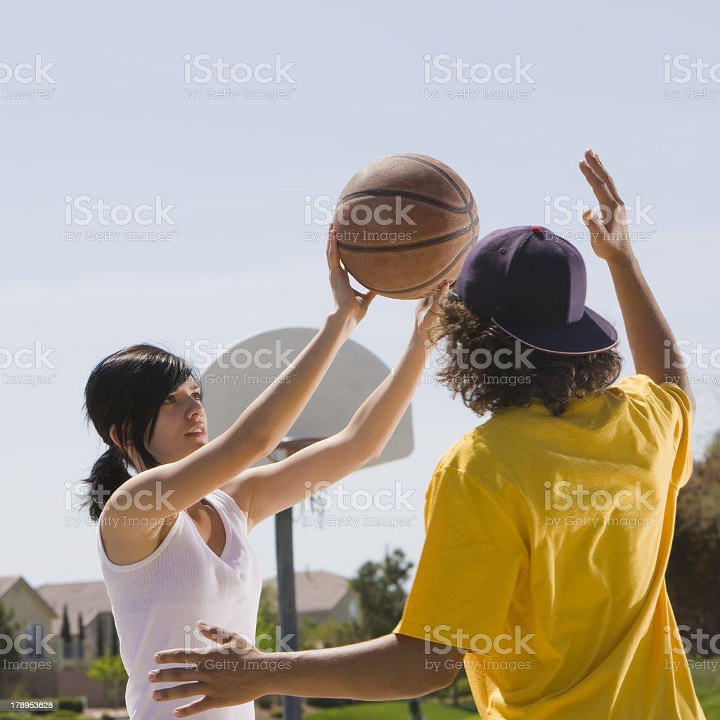 Two teens play basketball royalty-free stock photo