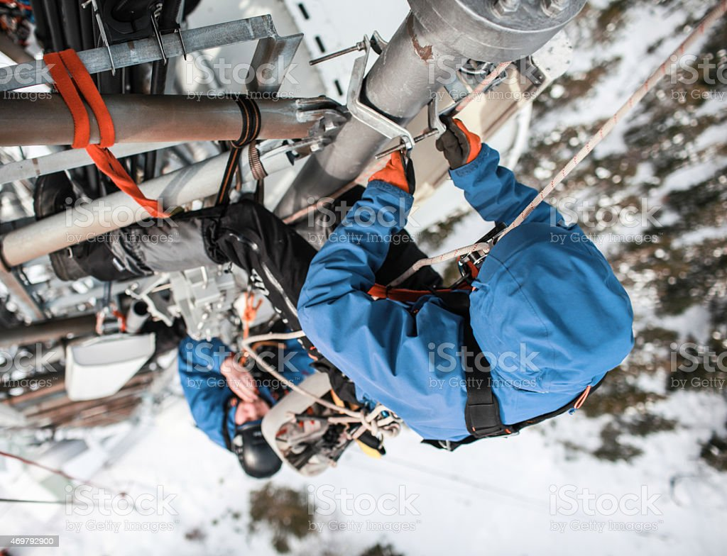 Two telecommunication manual high worker engineers repairing antenna stock photo