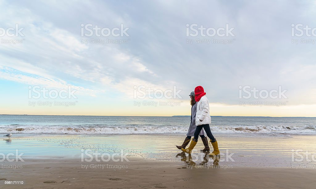 Two tennager girls walking at the beach stock photo