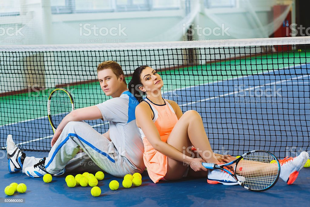 two tennis player relaxing next to a net stock photo
